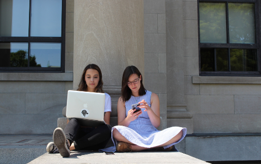 Two woman sitting outside and using electronic devices