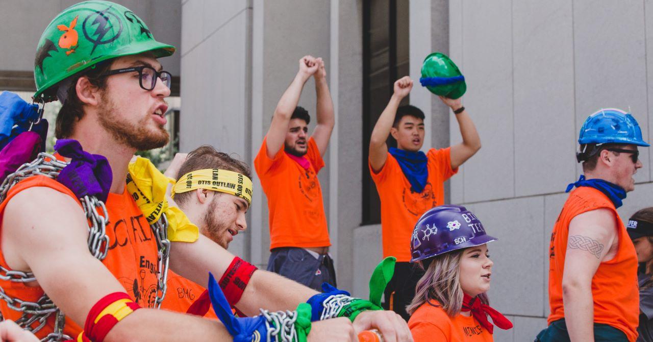 Des étudiants portant des casques de protection se réjouissent.