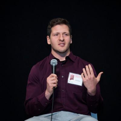 Un homme assit parlant au microphone