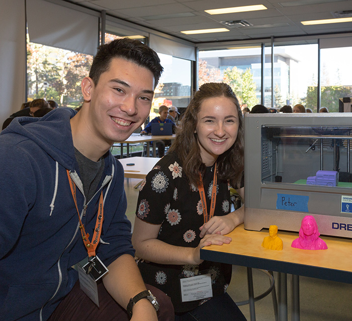 2 students using a 3-d printer