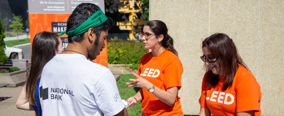 Two woman wearing orange shirts talking to students at an outside booth