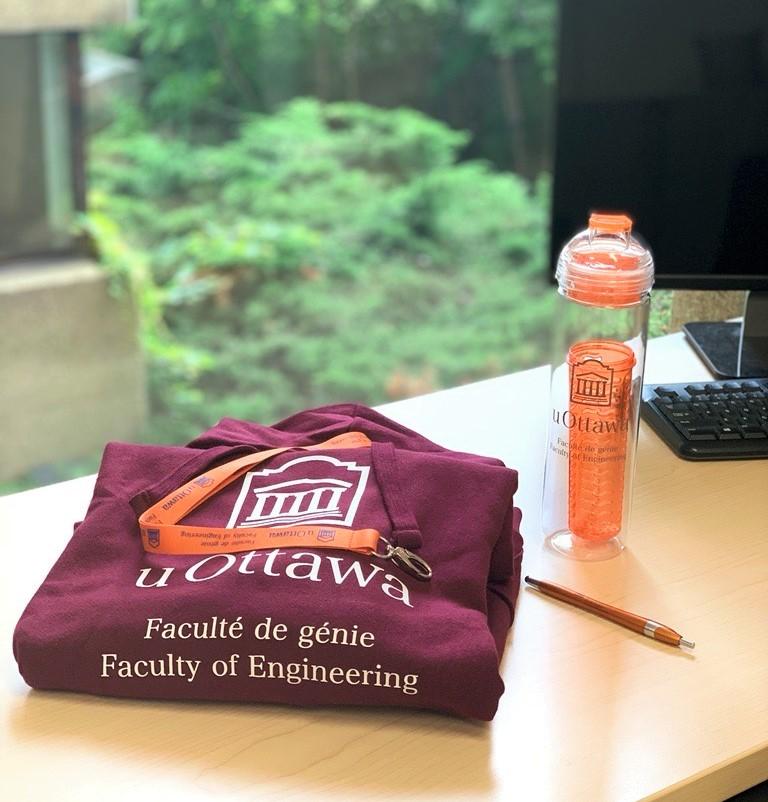 Une pile de cadeaux sur un bureau - un sweat-shirt, un porte-clés, une bouteille d'eau et un stylo.