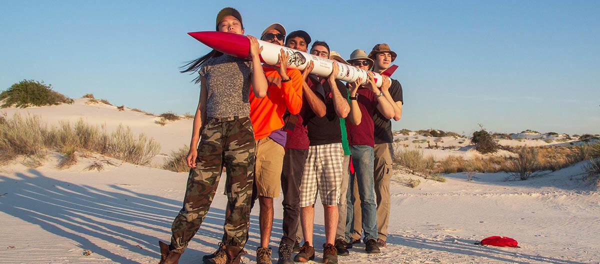 Un groupe d'étudiants tenant une fusée