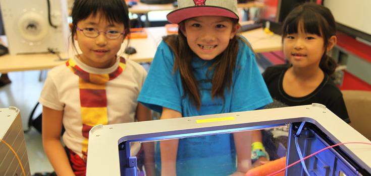 Teens peeking inside a 3D printer.