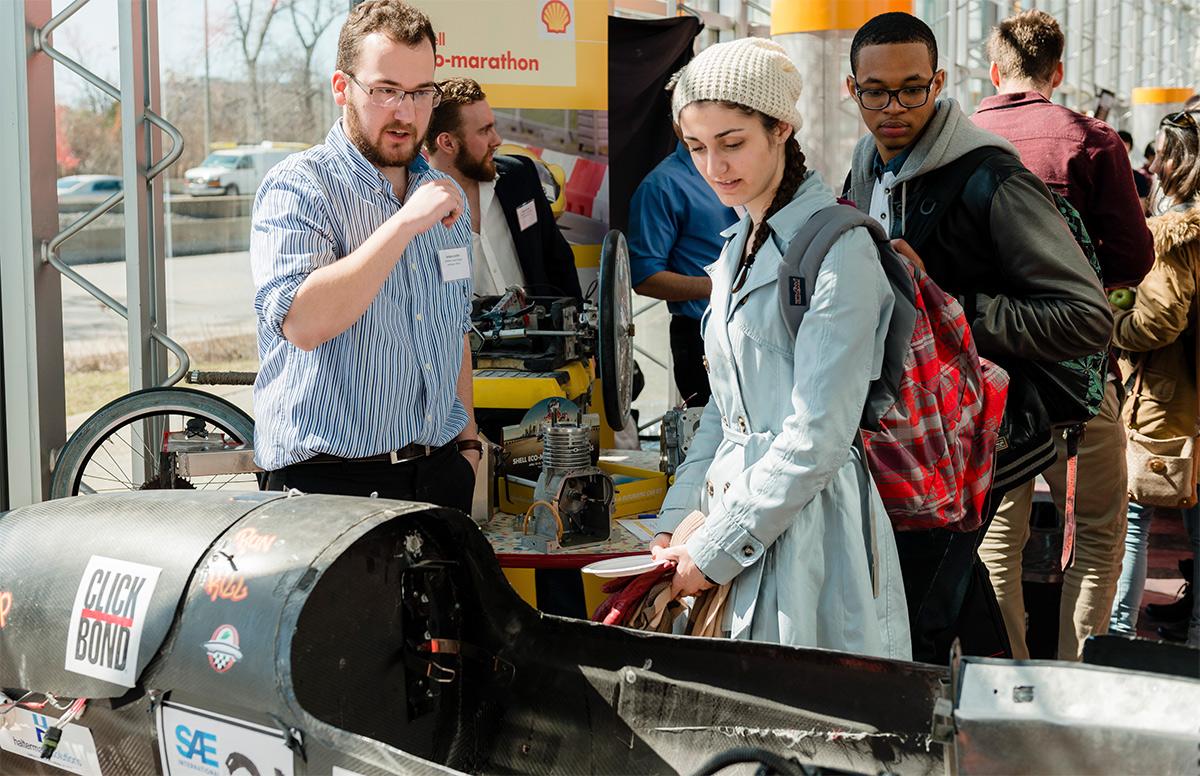 students looking at a car