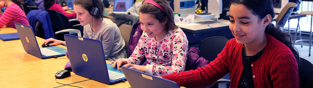 Girls working on a project with laptops