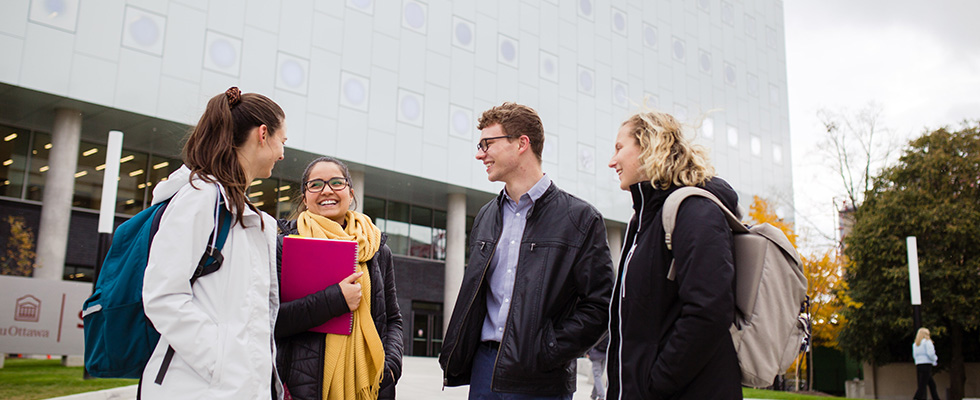A group of four students interacting together in front of a University of Ottawa building