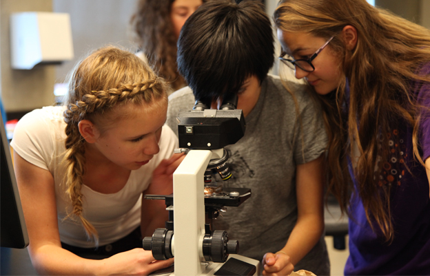 Students learning to use a microscope.