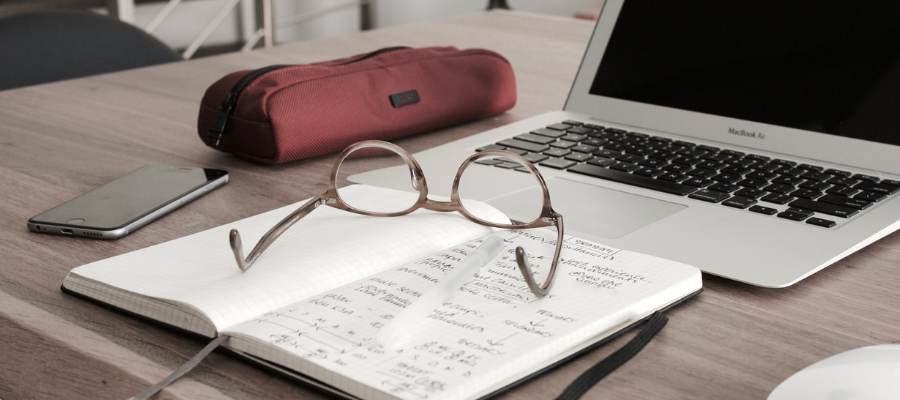 Notebook on a desk with glasses on top of it