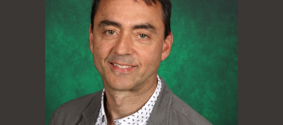 Picture of a middle-aged men in front of a green background